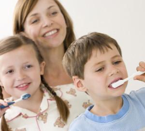 Mother watching children brushing teeth